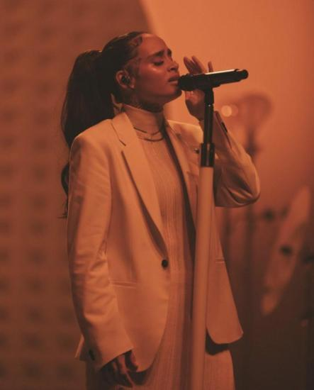 Image shows Kehlani in an all white suit holding a microphone, the lighting is red surrounding them.