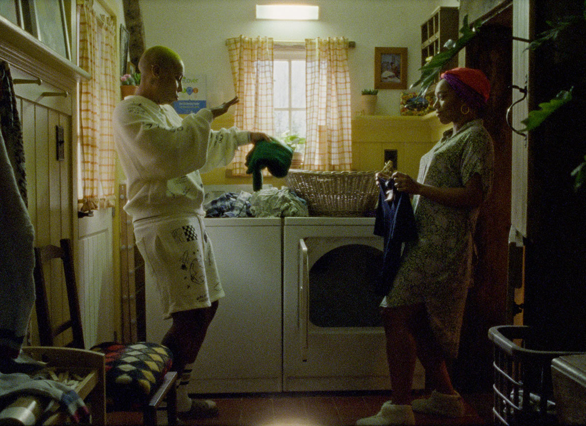 In a still from the third season of Master of None, Lena Waithe's Denise dances while doing laundry with Naomi Ackie's Alicia