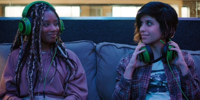 Mythic Quest queer gamers: Dana and Rachel sit on a couch with gamer headphones on smiling at each other.