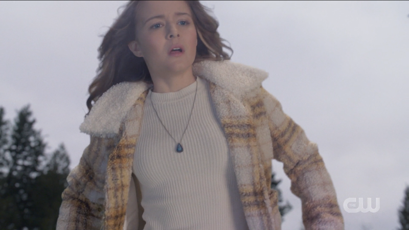Supergirl episode 606: Young Kara looks surprised while flying in a plaid fleece coat.