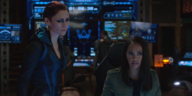 Screenshot from Supergirl: Alex and Kelly look down at the spaceship's interface.