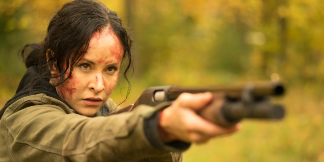 Tommie-Amber Price as Renee with blood on her face pointing a shotgun