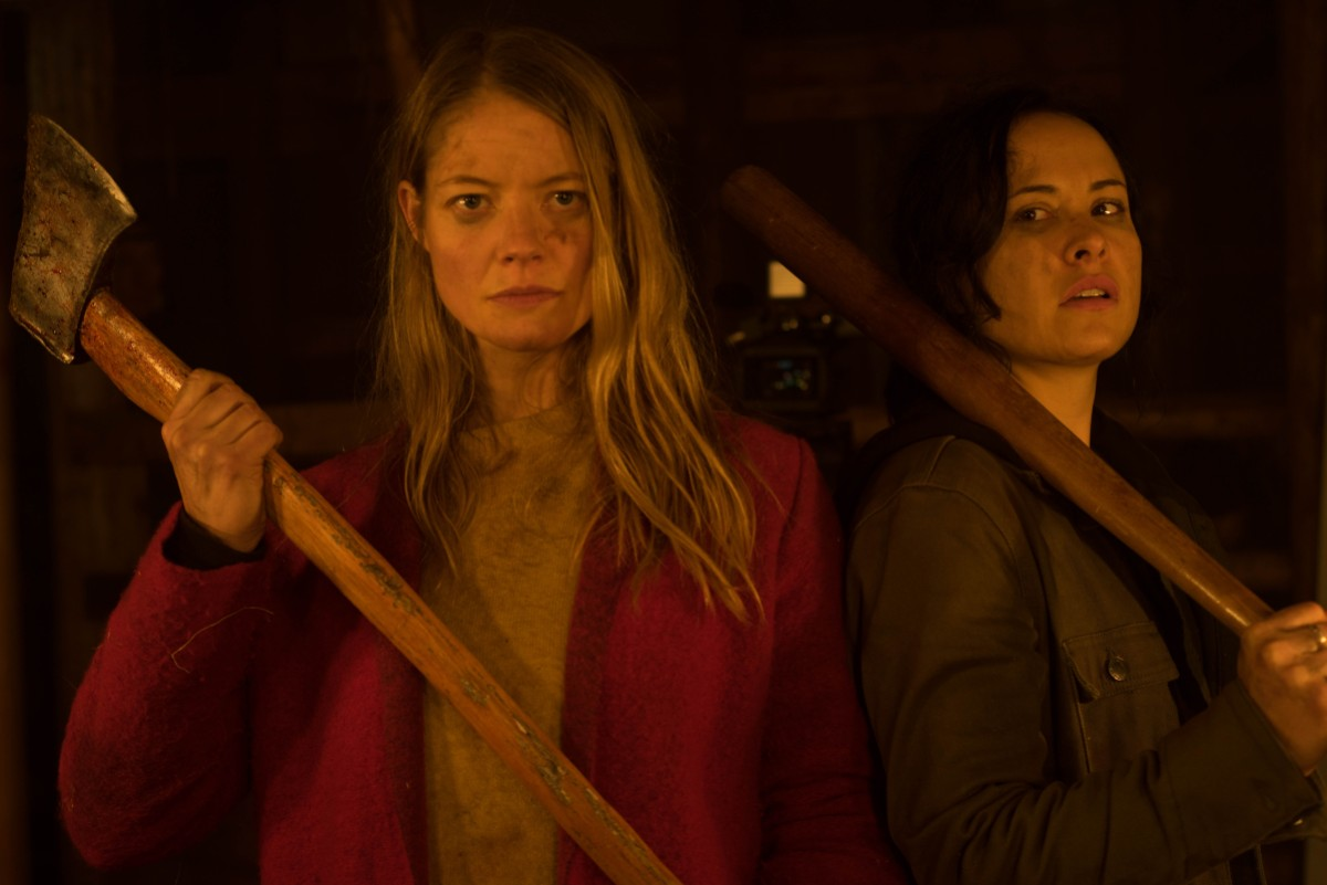 Valerie and Renee stand bloody and ready to fight each holding an axe