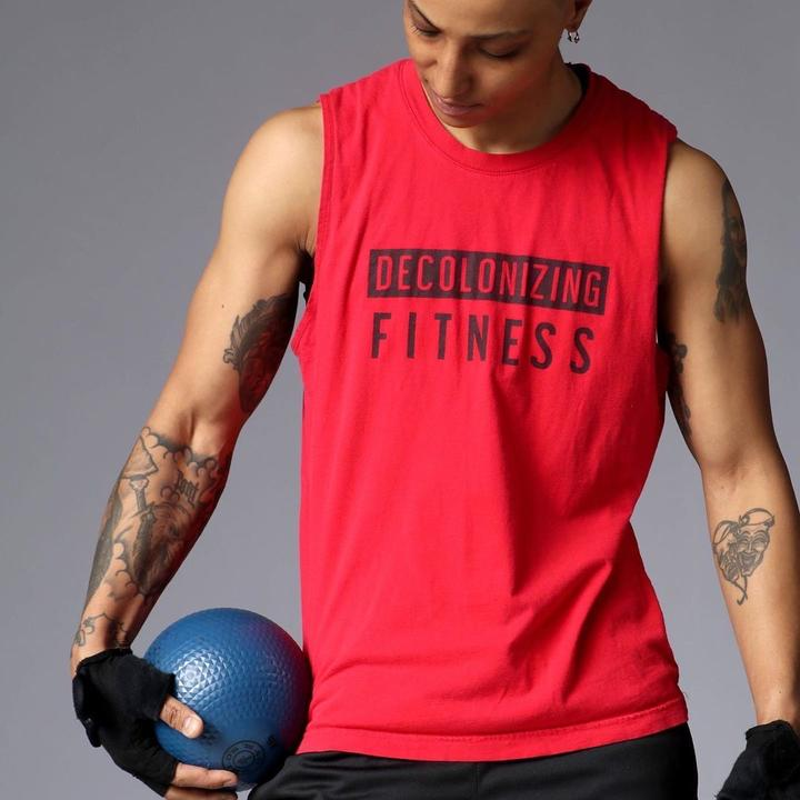 """Model wearing red muscle tee that says """"Decolonizing Fitness"""" on it in black lettering"""