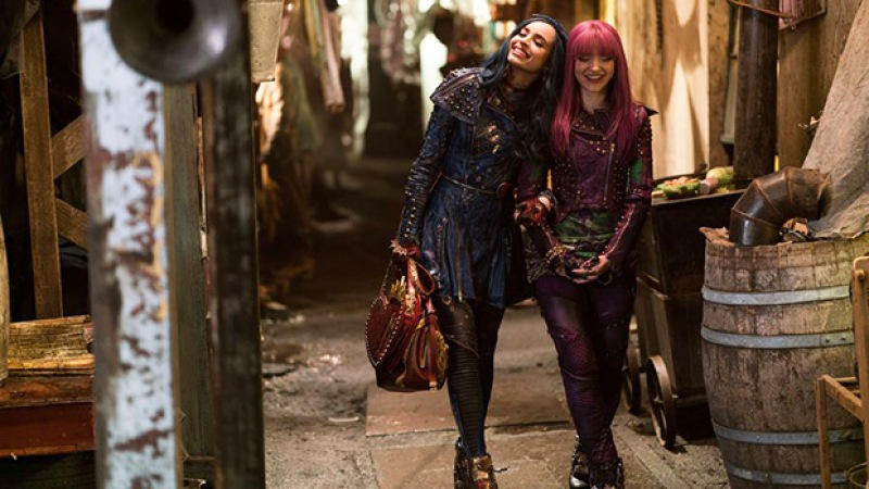 Bisexual Dove Cameron as Mal from Descendants. She is walking while holding hands with Evie, played by Sofia Carson.