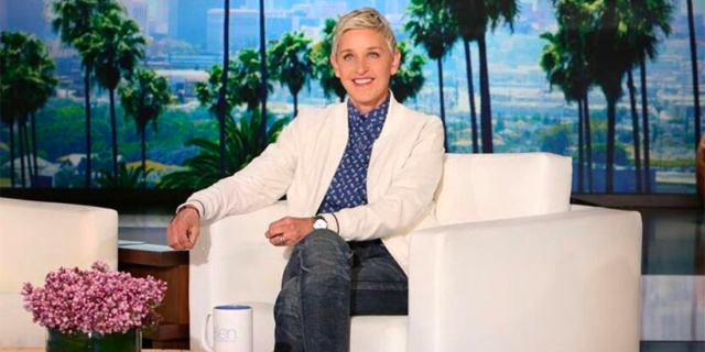 Ellen DeGeneres sits on the set of her talkshow in a white blazer, blue button-up, and jeans