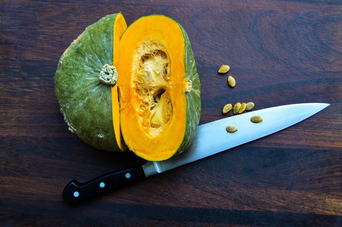 An overhead photo of a sliced kabocha squash with a chef's knife, with some of the seeds spilling onto the table.