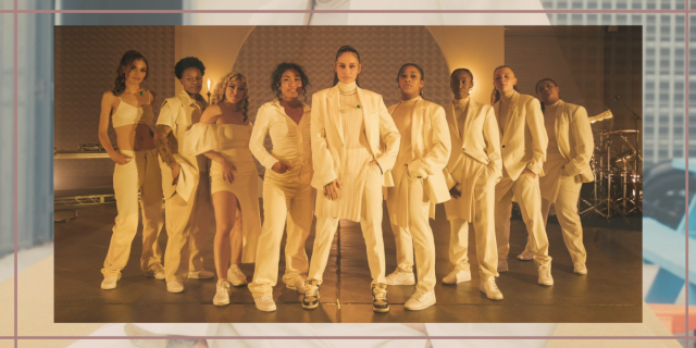 Image Shows Kehlani in her all white suit surrounded by their band who are also all wearing white.