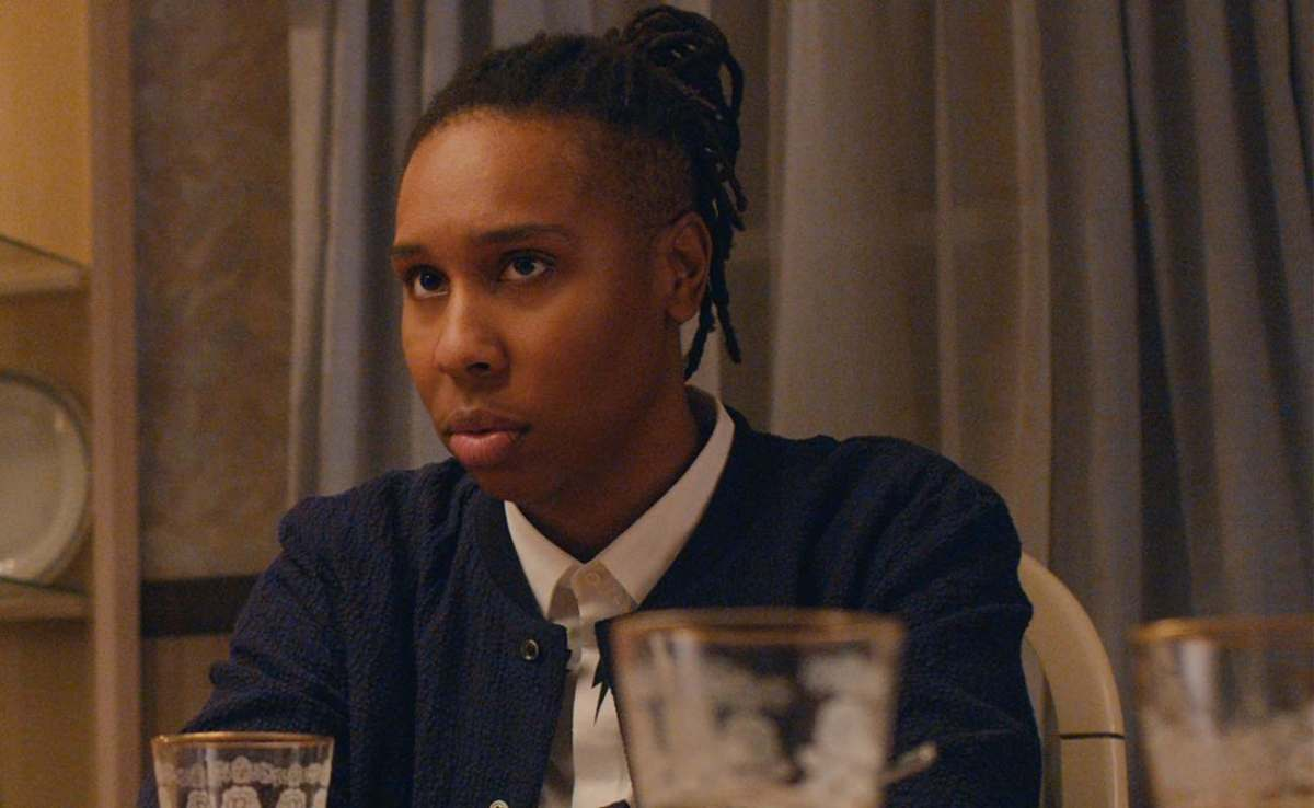 Lena Waithe in Master of None during the second season, she has dreadlocks pulled back into a high ponytail and a collard shirt underneath a bomber sports jacket. It is thanksgiving dinner and she is sitting at her mom's dinner table.