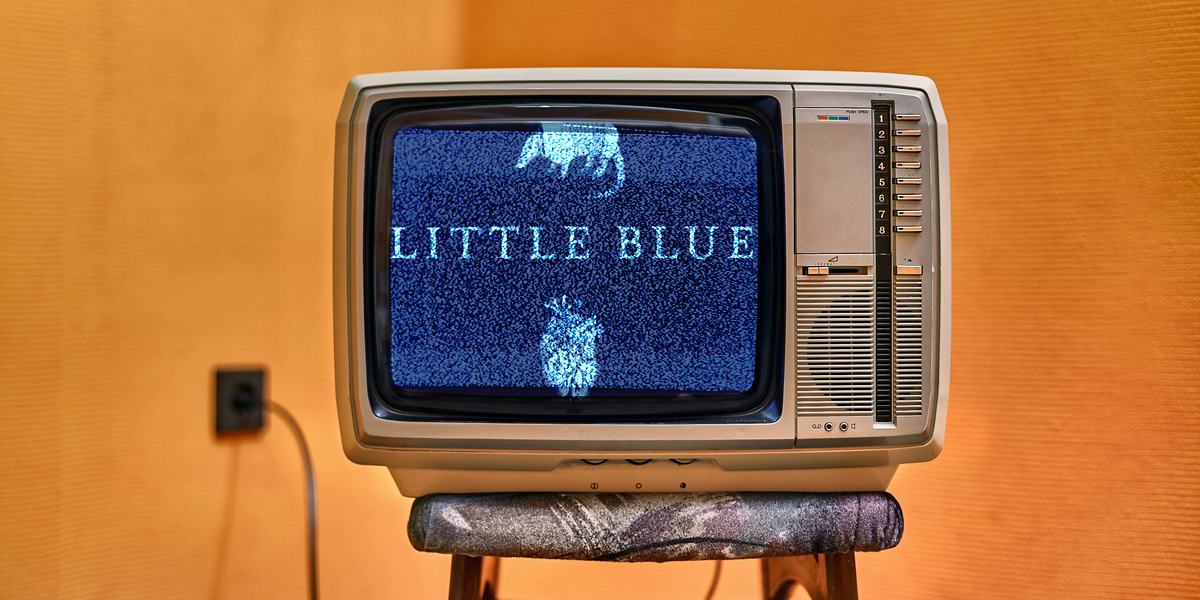 A vintage television set sitting on top of a stool in a warm-toned room with the text LITTLE BLUE showing on a static-y screen