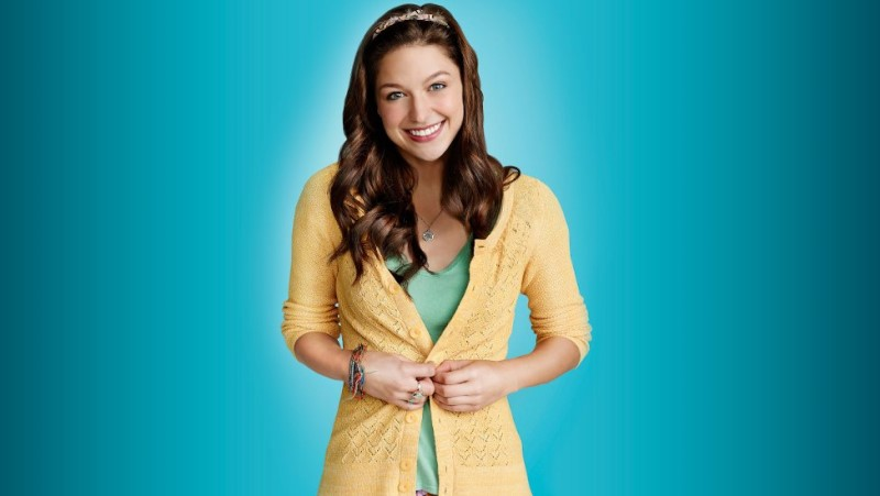 Sweet Marley Rose smiles wearing sunshine yellow against a clear teal background.