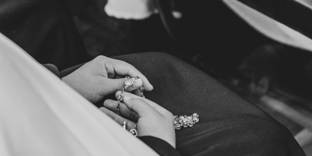 A black and white photo of a pair of hands holding a rosary in a lap.