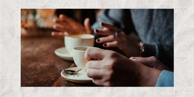 A photo of two women's hands holding coffee and gesturing at a brunch table laid over a newsprint background