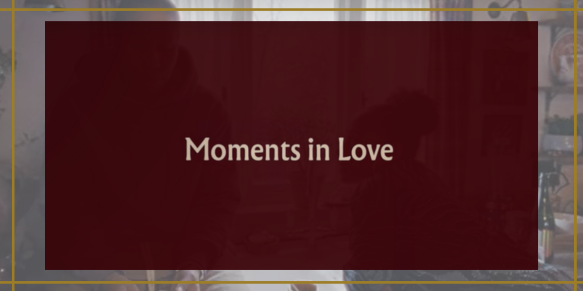 """Image shows a burgundy box that has the words """"moments in love"""" in the center with an image behind it that shows two people in a kitchen"""