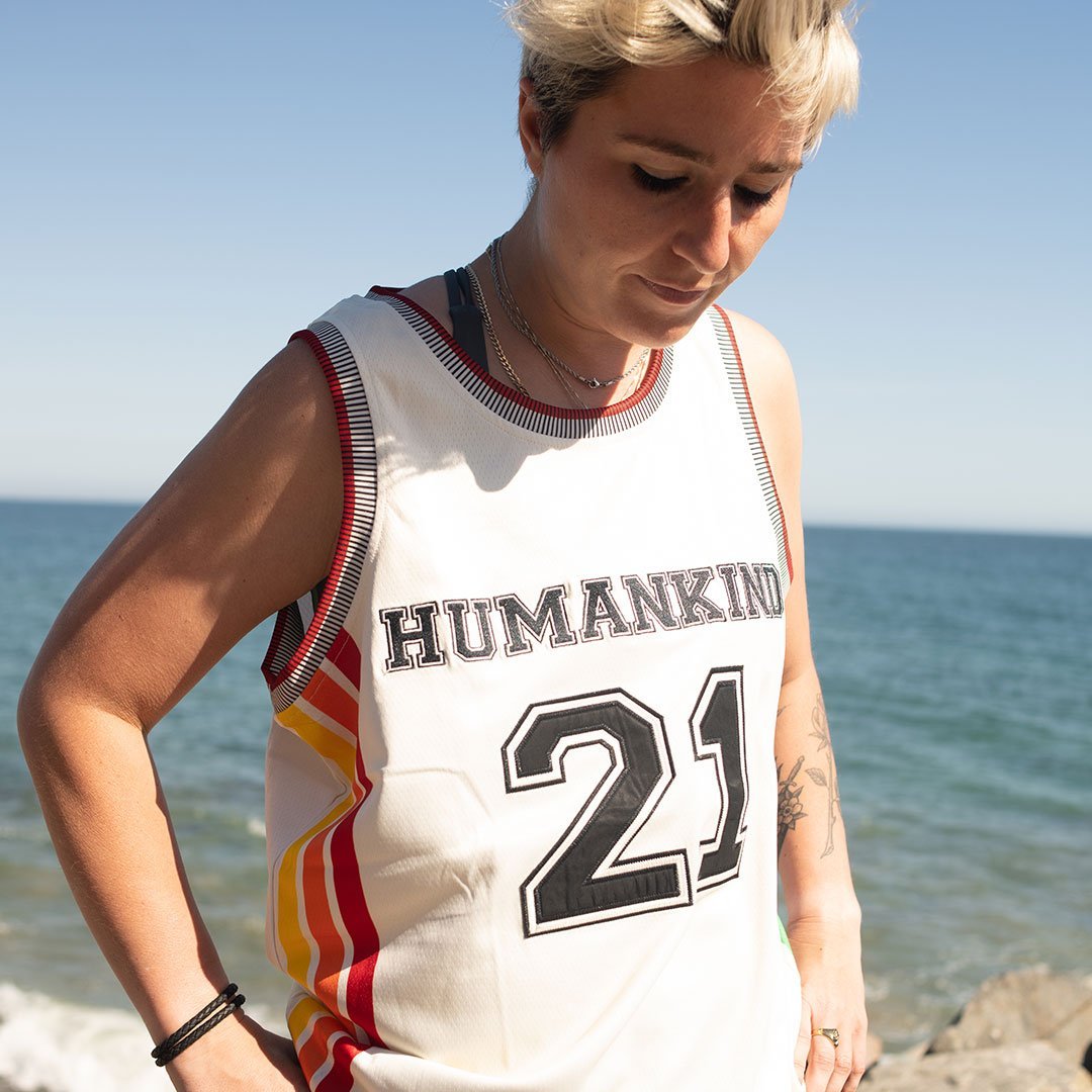 """Model at the beach wearing a jersey that says """"HUMANKIND"""" on the front with the number """"21"""" beneath it in block lettering."""