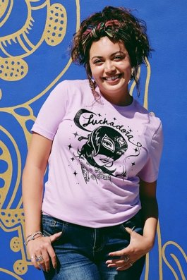 """Smiling model in front of a blue wall, wearing a lavender t-shirt that says """"Luchadora"""" in script above an illustration a woman in a mask."""