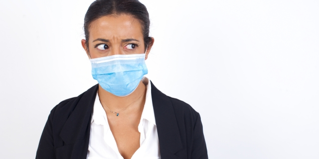A woman in professional dress looks unsettled while wearing a disposable paper mask over her nose and mouth.