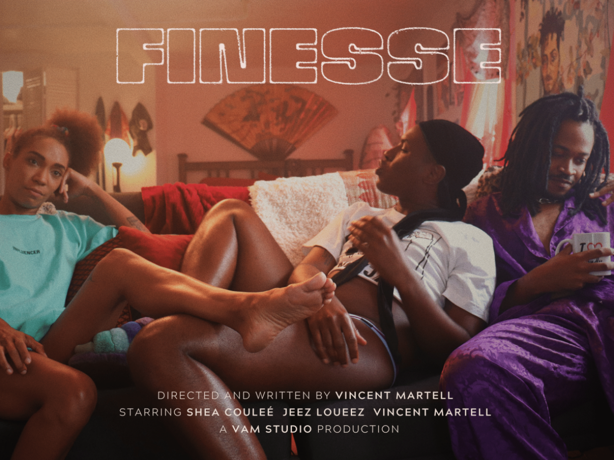 Image shows three Black people lounging on a couch. They are resting their legs one each other while their living room is in the background filled with lamps that have scarves draped over them and other decor.