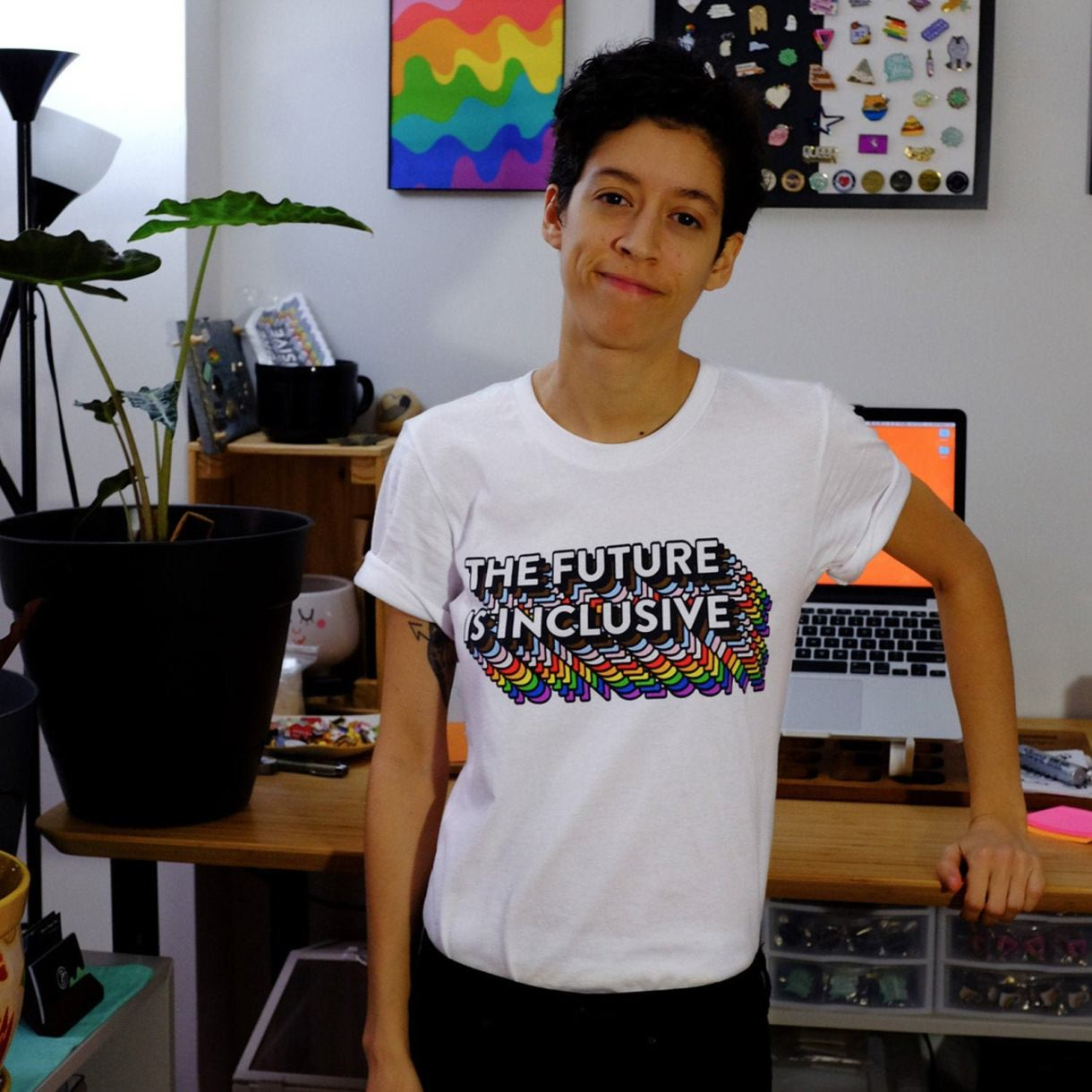 Model in an office wearing a white tee with the words THE FUTURE IS INCLUSIVE with rainbow shading