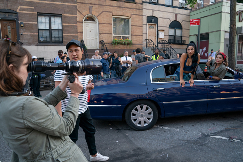 Behind the scenes of In the Heights, Stephanie Beatriz and Daphne Rubin-Vega are in the back of a black town car while director Jon Chu directs