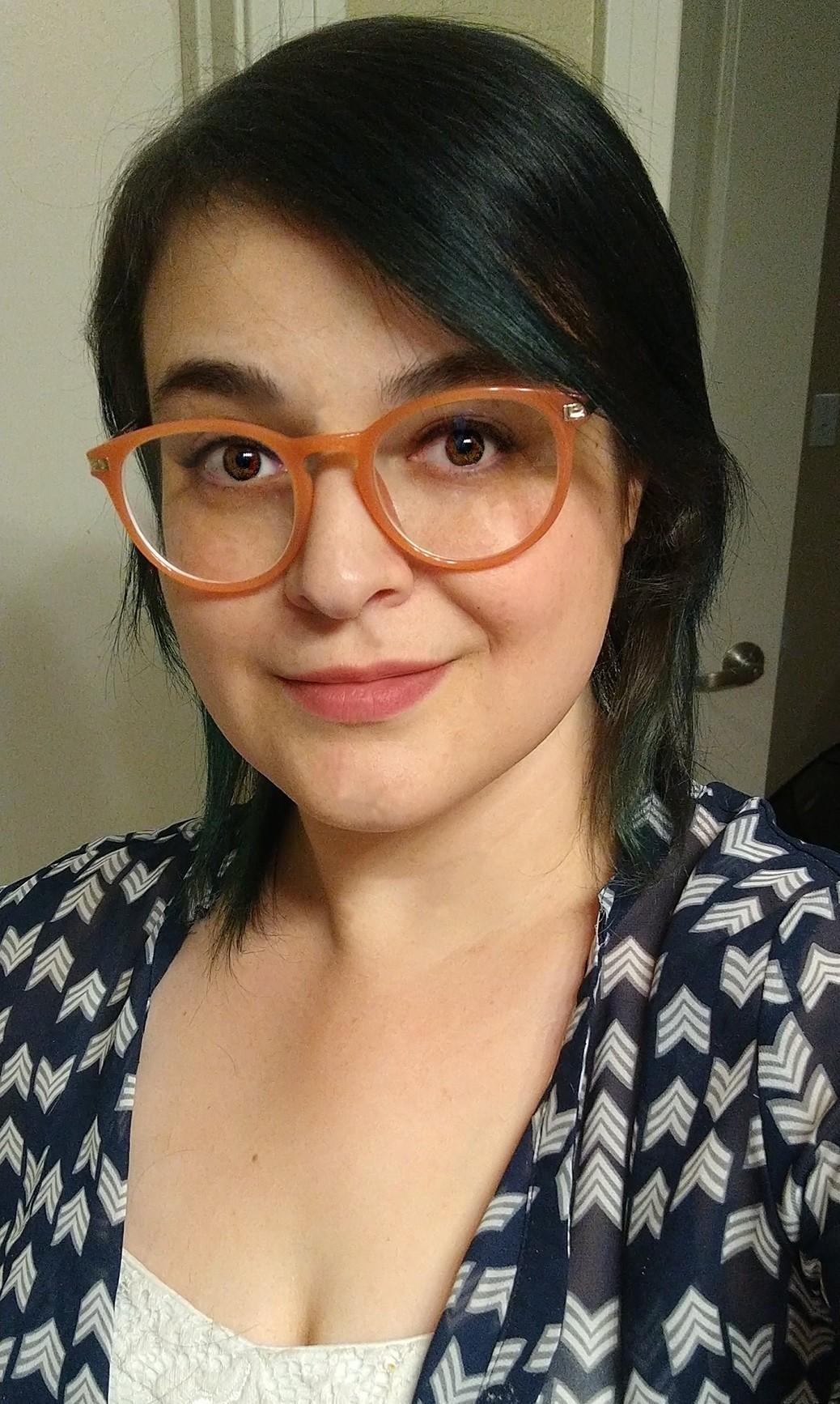 Stacie wears orange rim glasses for a selfie