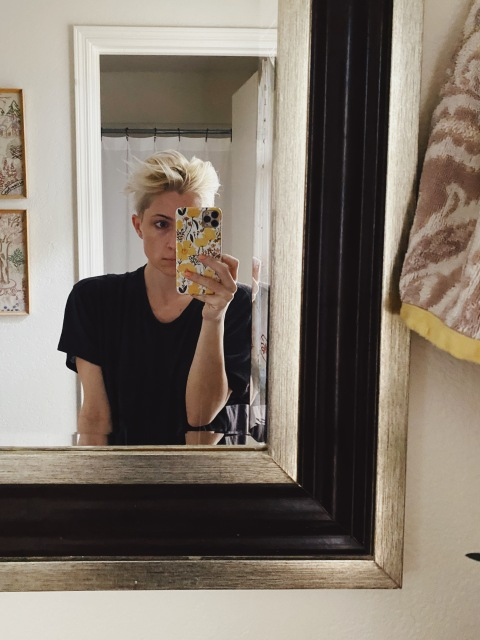 Laneia taking a selfie in front of her bathroom mirror, wearing a black tee shirt