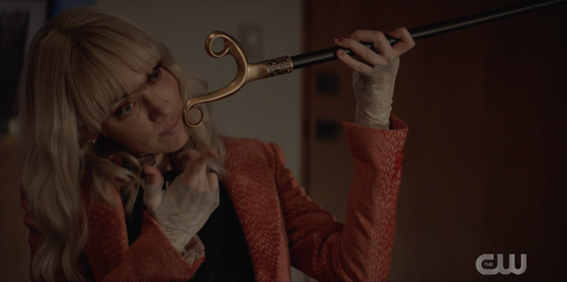 Alice with a cane being held to her head like a weapon