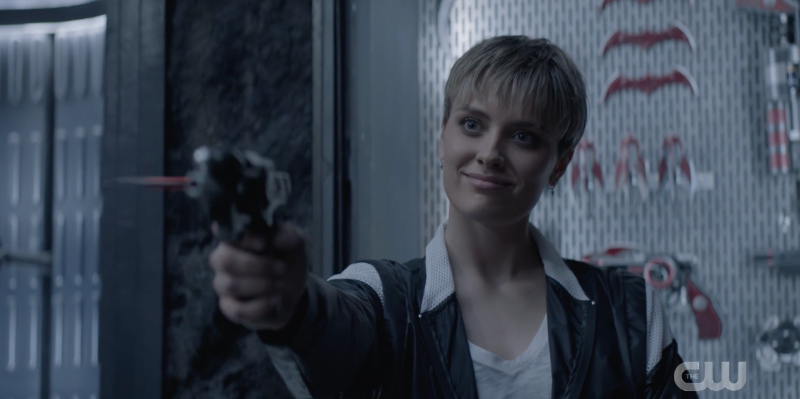 Wallis Day points a gun in the Batcave