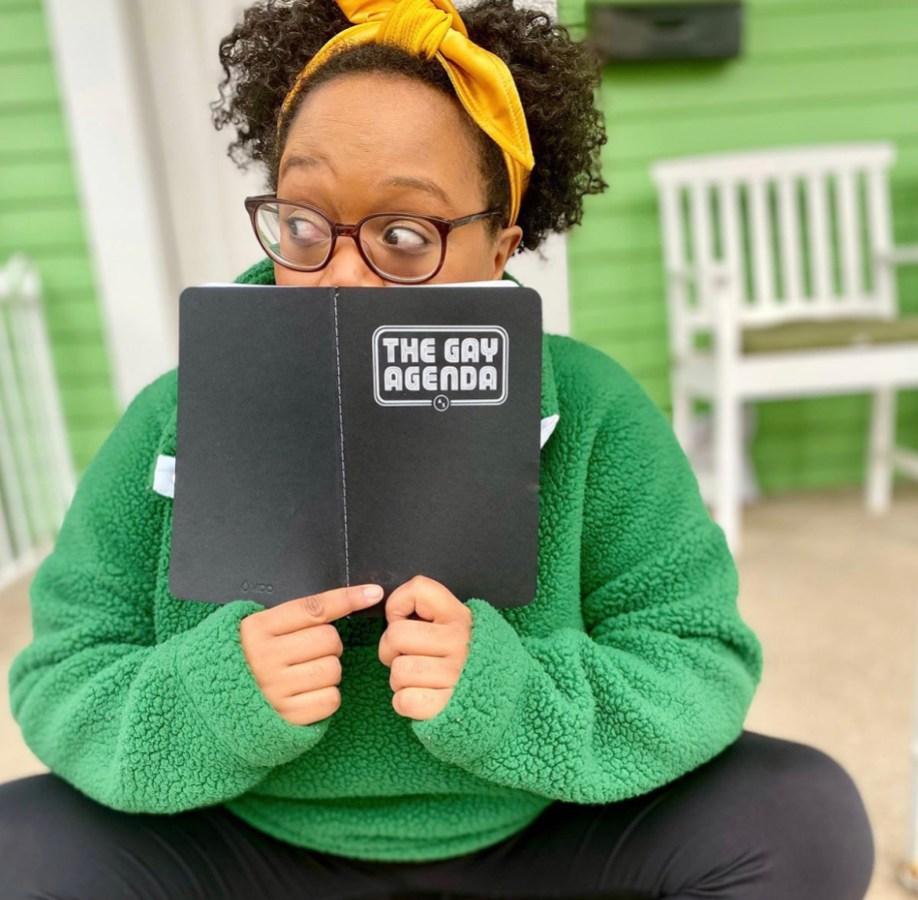 Carmen reading her gay agenda in a green jacket