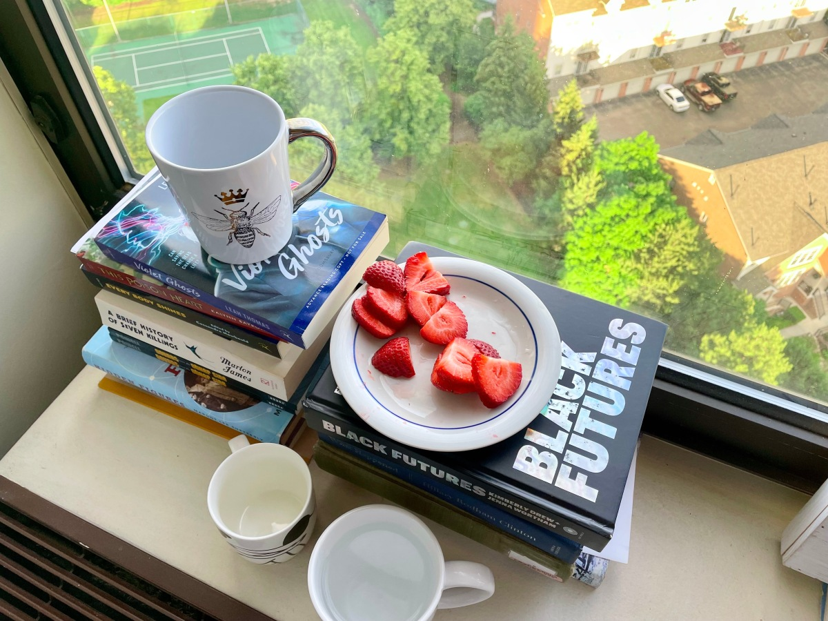 There are three mugs and a pile of cut up strawberries on top of books