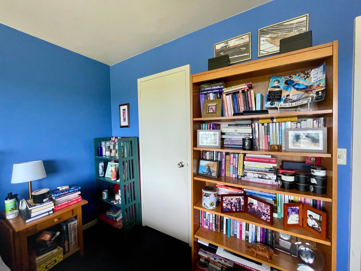 A photo of Carmen's bookshelf, which is piled high with books, alongside her altar full of candles and another pile of books on her nightstand.