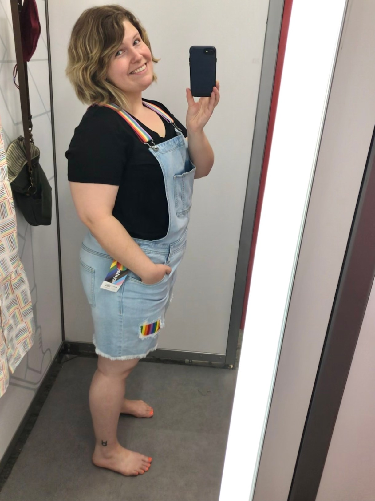 Caley posing in denim overalls in front of a mirror taking a selfie