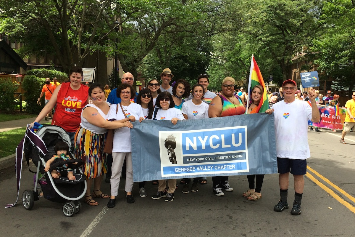 A group of people, including the author and her family, stands in the street, smiling and carrying a large sign for NYCLU