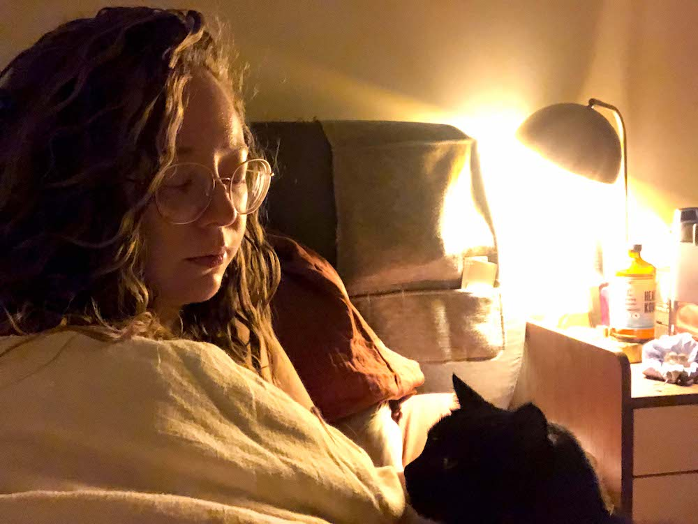 A dimly lit photo of Rachel sitting up in bed, with a nightstand visible behind her and a small black cat visible in the foreground
