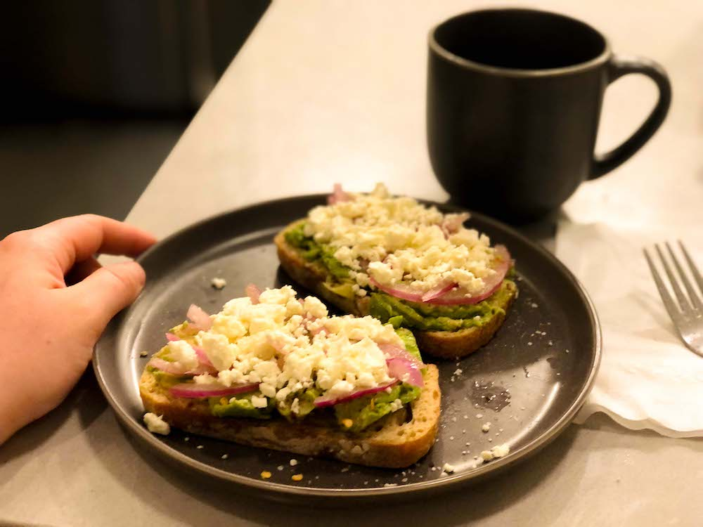 A closeup photo of two slices of avocado toast on a gray plate with a matching gray coffee cup, which Rachel's hand steadies on a kitchen counter