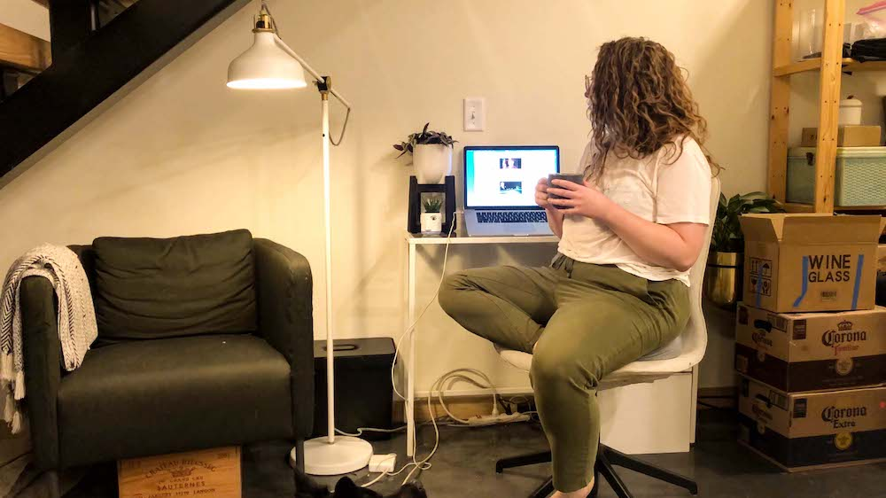 Rachel, a white woman with curly hair wearing green sweatpants and a white t-shirt, is sitting at a small white desk next to a lamp, armchair and a pile of unpacked moving boxes. She's turned to the side, cupping a cup of coffee while looking at her laptop screen.