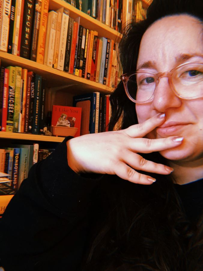 Vanessa faces the camera, hand over mouth, wearing a black shirt. Vanessa is a white woman, with glasses and long brown hair.