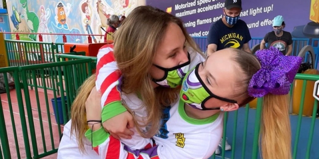 Jojo Siwa is in a Toy Story themed face mask and is kissing her girlfriend in an amusement park (who is also wearing a Toy Story face mask)