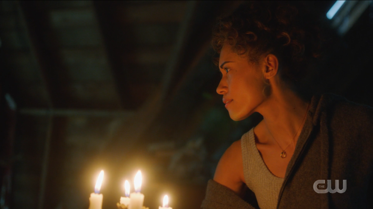 Astra holds a candelabra as she walks through a dark and dusty attic.
