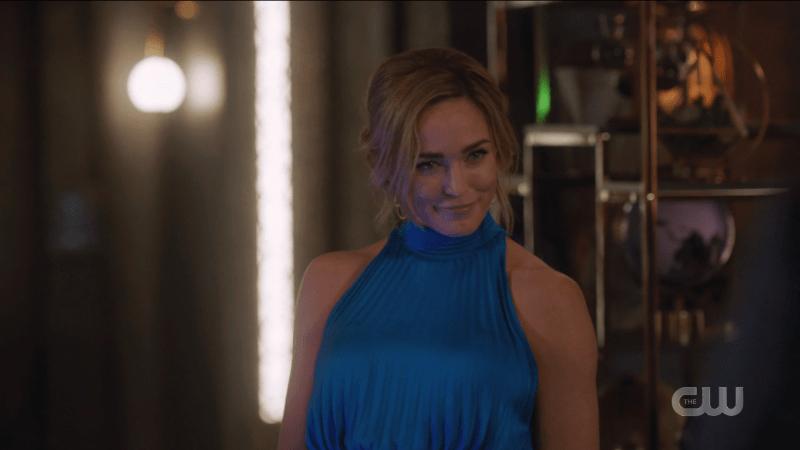 Sara smirks in her blue blue dress.