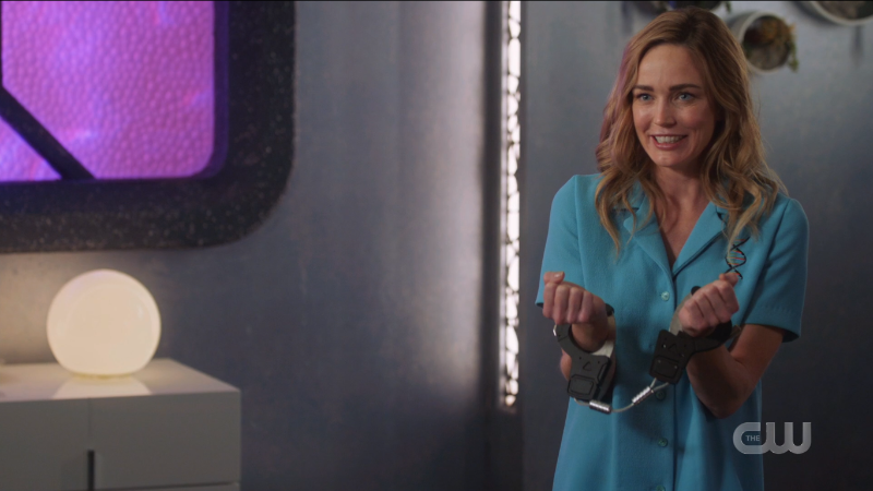 Sara smiles while holding out her handcuffed wrists.