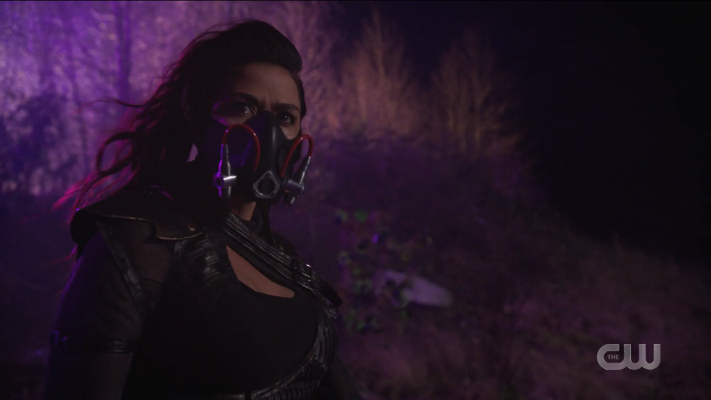 Kayla stands in the purple wasteland with her mask on and it's very attractive.