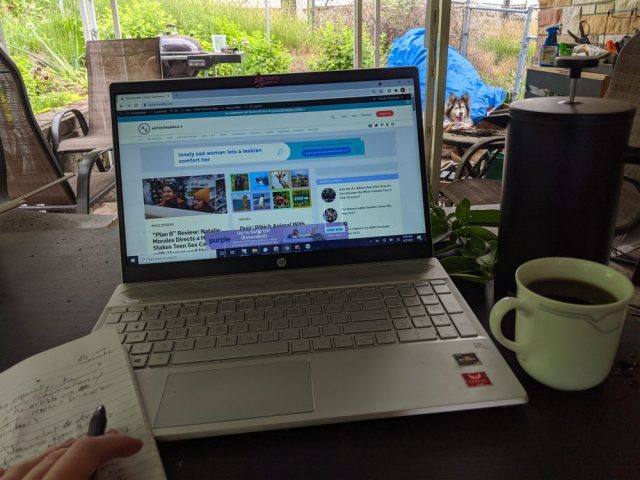 Nicole's computer is open on a table to Autostraddle.com. It's outside. Mya lookson way off in the background.