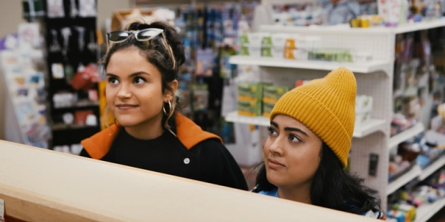 A still from the movie Plan B, with Lupe and Sunny standing at pharmacy looking for Plan B.