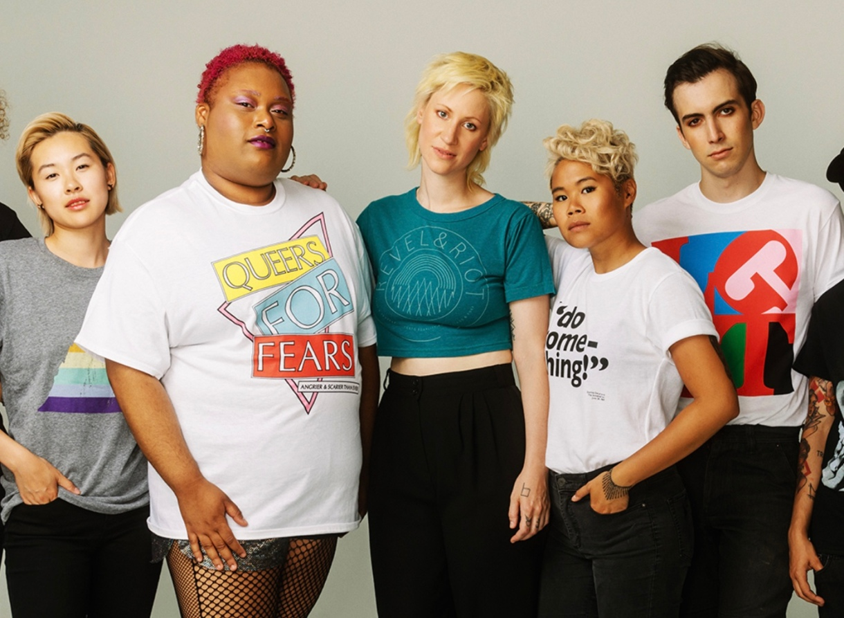 """Models in Revel + Riot tees: a grey shirt with a triangle rainbow, a white shirt with """"QUEERS FOR FEARS"""" in yellow, blue and red blocks, a dark teal Revel + Riot shirt, a """"Do something!"""" shirt and an LGBT art shirt."""