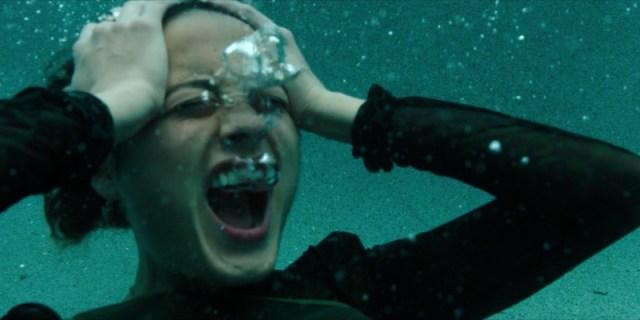 Riley fully dressed in her pool screams underwater hands on her head
