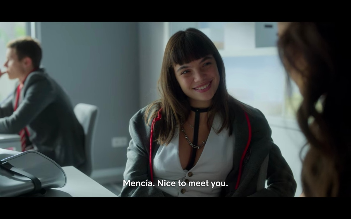"""Mencia in a white vest and a leather situation saying """"Mencia, nice to meet you"""" in class to Rebe"""