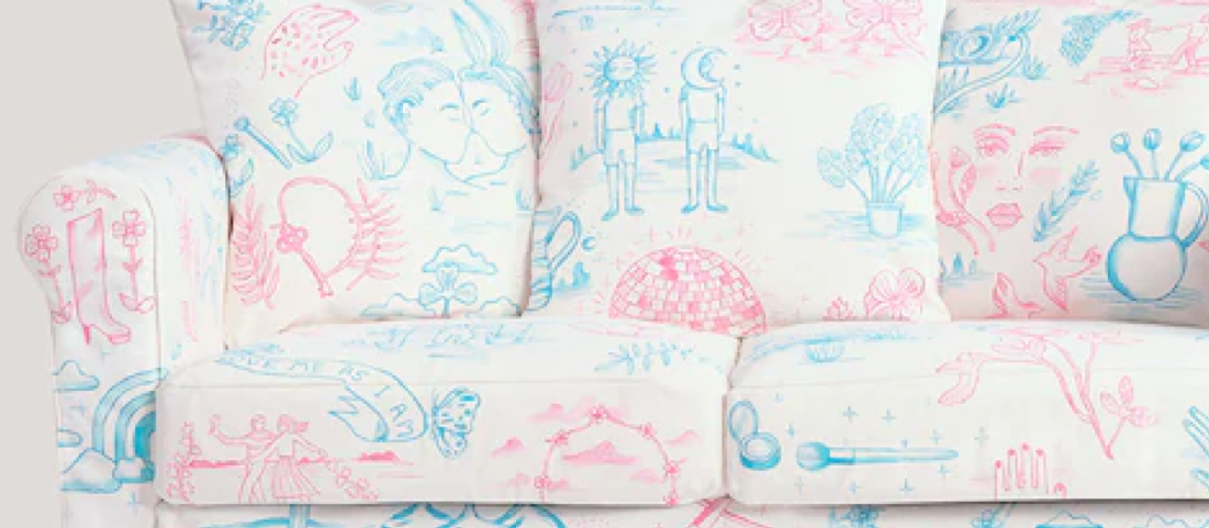 A close up of the trans pride couch, in pink and blue colors depicting line drawings of various images