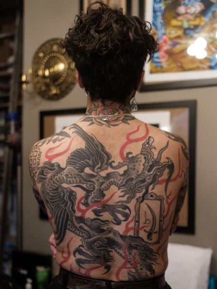 Image shows the heavily tattooed back of Sema.