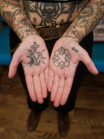 Image shows the tattooed palms of Sema. Their hands are together and opened with palms facing upward.